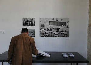 A visitor browses through the selection of photos at the exhibition. © UNRWA Photo by Alaa Ghosheh