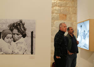 Visitors browse through the selection of photos at the exhibition. © UNRWA Photo by Alaa Ghosheh