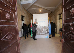 A visitor makes a playful gesture as he reacts to a banner welcoming guests to the exhibition. © UNRWA Photo by Alaa Ghosheh