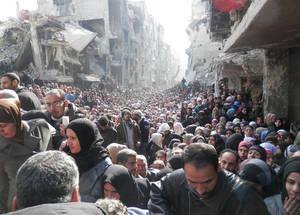 في كانون الثاني 2014، عندما كانت الأونروا قادرة على إكمال أول عملية توزيع إنساني لها في اليرموك بعد ما يقارب من ستة أشهر من الحصار، استقبلها الآلاف من السكان اليائسين في الشارع الرئيسي المدمر. الحقوق محفوظة للأونروا 2014.
