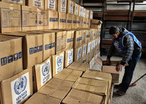 Access to Neirab has been frequently cut by armed conflict in the surrounding area, impacting on the ability of UNRWA to distribute critically-needed food and household assistance. A worker stacks boxes in the UNRWA distribution centre in Neirab. February 2015. © 2015 UNRWA Photo by Ahmad Abu Zeid
