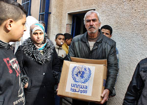 Ali Joma Al-Khatib, aged 67, uses his food parcel to help support his wife and nine sons. The family is struggling financially; Ali's wife is suffering from heart disease and his eldest son was displaced from his home in rural Aleppo. Ali currently has no other income to cover the family's daily living costs. February 2015. © 2015 UNRWA Photo by Ahmad Abu Zeid