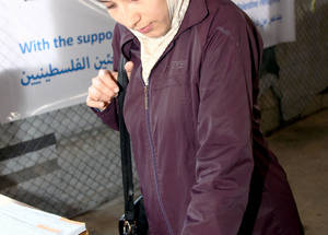 "For Shahnaz Ghneim and her family, food assistance provided by UNRWA, made possible by the generous support of the UAE, is a lifeline. Shahnaz is expecting her second child. ""We do not have enough money to buy baby clothes and diapers. The food basket helps us during this difficult time,"" she says. Alliance Distribution Center, Damascus, November 2014. © 2014 UNRWA Photo by Taghrid Mohammad"