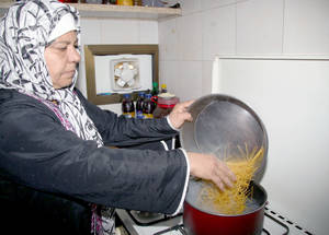 UNRWA monthly food packages, made possible by the generous support of the UAE, contain staple foodstuffs including pasta, lentils, rice, cooking oil, milk powder and sugar. Here, a woman cooks pasta from her package for her evening meal. Damascus, November 2014. © 2014 UNRWA Photo by Taghrid Mohammad