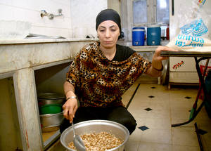"Food assistance from the UAE helps the most vulnerable refugees, including female-headed households. Nisrine Farhat uses the lentils and rice from her UNRWA/UAE food package to cook her favourite dish of moujadara. ""It is easy, fast and delicious. The food basket brings food to my family at this extremely difficult time,"" she says. Damascus, November 2014. © 2014 UNRWA Photo by Taghrid Mohammad"