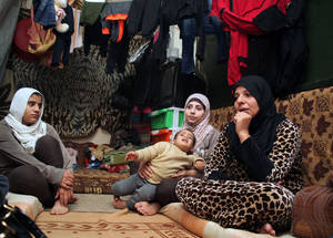 Many Palestine refugees live in accommodation which offers little protection from the seasons. These family members are among the 11.868 displaced Palestine refugees and Syrians living in temporary UNRWA collective shelters. They share a re-purposed classroom with three other families. © 2014 UNRWA Photo by Taghrid Mohammad.