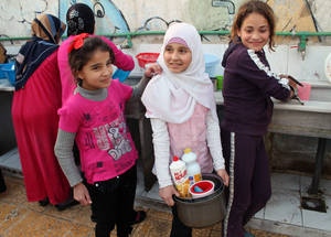 UNRWA made adjustments to the shelters to provide additional kitchen, bathroom and washing facilities to accommodate the needs of displaced refugees. These three girls in the Jaramana collective shelter are washing their dishes at repurposed sinks. ©2014 UNRWA Photo by Taghrid Mohammad