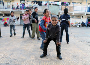 Children playing in the former schoolyard at Douma Collective Shelter, Damascus. © 2014 UNRWA Photo by Taghrid Mohammad