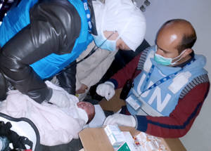 طبيب يقوم بفحص مريض صغير في نقطة صحية مؤقتة في منطقة اليرموك المحاصرة. وتقوم الأونروا بتشغيل 12 مركزا صحيا إلى جانب 12 نقطة صحية أخرى في سائر أرجاء سورية من أجل خدمة السكان من اللاجئين الفلسطينيين، سواء ممن يستقرون في تلك المناطق أو ممن نزحوا إليها. وتشمل تلك النقاط نقطة صحية مؤقتة في منطقة اليرموك المحاصرة التي يقوم فيها هذا الطبيب الواضح في الصورة بفحص مريضه الصغير. الحقوق محفوظة للأونروا 2015.