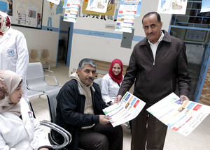 UNRWA staff share community education materials at South Baqa'a health centre in Jordan. © UNRWA Photo