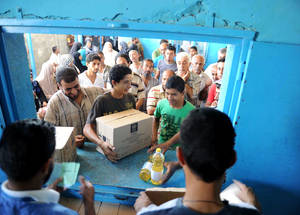 IRUSA and UNRWA are working together to alleviate alarming levels of  food insecurity by distributing food packages to over 868,000 Palestine refugees in the Gaza Strip on a quarterly basis. Here, a teenager collects cooking oil from the UNRWA food distribution centre in Jabalia Camp. Photo: © 2014 UNRWA photo by Shareef Sarhan