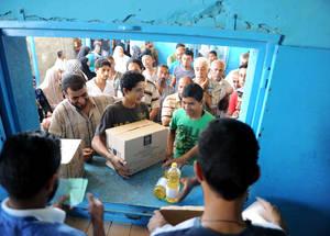 تعمل مؤسسة الإغاثة الإسلامية الأمريكية والأونروا جنبا إلى جنب من أجل التقليل من المستويات العالية من انعدام الأمن الغذائي عن طريق نوزيع الطرود الغذائية لأكثر من 868,000 لاجئ فلسطيني في قطاع غزة وذلك على أساس ربع سنوي. والصورة هنا تظهر مراهقا يتسلم زيت طهي من مركز الأونروا لتوزيع الغذاء في مخيم جباليا. حقوق الطبع محفوظة للأونروا. تصوير شريف سرحان، 2014.