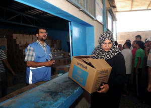 Handling of emergency food distribution is often the responsibility of mothers who carefully ration the amounts of rice, flour, milk, cooking oil and canned meat among family members on a daily basis. Here, an UNRWA food distribution worker ensures each emergency food parcel provided has been packed accordingly. © 2014 UNRWA photo by Shareef Sarhan