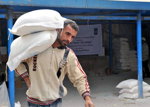 Standard UNRWA emergency food packages contain 30 kilograms of rice and flour per person. Here, flour is being carried into the Beach Camp distribution centre. © 2014 UNRWA photo by Shareef Sarhan