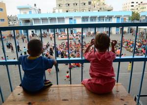 Two young children watch CMHP activities at the Bahrain Collective Centre in Gaza where they continue to find temporary shelterafter their family homes in al-Shuja'iyyah were destroyed in the conflict. Some 300,000 internally displaced persons sought shelter at UNRWA collective centres at the height of 2014 summer hostilities. © 2014 UNRWA Photo by Fadi Thabet