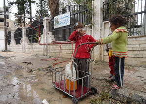 Residents fill tanks that they carry on makeshift carts or strollers back to their homes. April 2015. © 2015 UNRWA Photo by Rami al Sayyed