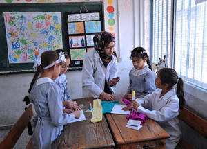 "Teachers, school principals and counsellors involved in the art project agree that the positive impact of the classes is already noticeable among the students, particularly regarding their social behaviour. ""At the beginning of the year, the students refused to work in groups, they were all very isolated. They had to learn how to share, how to work in teams and how to be open to new suggestions,"" said art teacher Marwa Al Assar. © 2015 UNRWA Photo by Khalil Adwan"