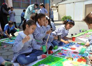 """تقول مي مراد، والتي بدأت برسم وتلوين الزهور والغيوم على جدران وأبواب المدرسة التي تعمل بها في مخيم الشاطئ لإضفاء بعض الألوان على حياة الأطفال اللاجئين: """"قبل أن نبدأ بهذه الحصص، كانت البيئة المدرسية باهتة، وواجه الطلبة صعوبات في التركيز والانتباه."""" وأضافت: """"في صفي، هناك طالبة واحدة كانت نادرة الابتسام؛ بدأتُ بإشراكها في أنشطة الرسم ومع مرور الوقت أصبحت شخصاً مختلفاً. اليوم، هي طالبة نشيطة ولديها أصدقاء، تحب المدرسة، والأهم من ذلك كله: أنها تبتسم."""" غزة - الحقوق محفوظة للأونروا 2015/ خليل عدوان"""