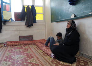 "Refugee Hazar Abu Jazar, sitting next to her son on a mattress in the classroom that has been her home for the past eight months, explained how she dreamed about leaving the collective centre and moving back to her old home. Yet once when she arrived at her home, she realized everything was destroyed. ""The door of the house was closed as I left it, but when I opened it, nothing remained, everything was destroyed. There was complete emptiness,"" she said. © 2015 UNRWA Photo by Khalil Adwan"