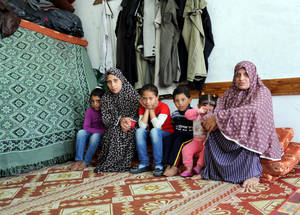 "Mona El Serawi, 36 (right), fled with her family from the extensively-shelled neighbourhood of Shujjaiya to the UNRWA collective centre in Rimal at beginning of the 2014 conflict. They have now sheltered there for over eight months. ""I hope so much that we can soon move out and have our own house and space. We have been waiting so long already. However, it will be difficult to say goodbye to the other families, with whom we went through such difficult times,"" she said. © 2015 UNRWA Photo by Khalil Adwan"