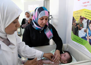"Ghina's mother had heard about the MMR vaccination on television. ""The vaccines will save the life of my daughter and protect her against the spread of disease,"" she said. © 2015 UNRWA Photo by Taghrid Mohammad"