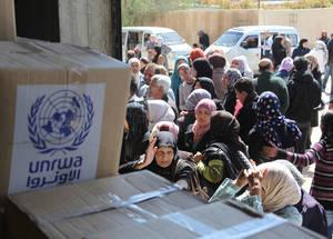منتفعون يصطفون من أجل الحصول على المعونة الغذائية أمام مركز توزيع تابع للأونروا في صحنايا بدمشق. إن أكثر من 95% من إجمالي لاجئي فلسطين الذين لا يزالون في سورية والبالغ عددهم 480,000 لاجئ يعتمدون على الأونروا من أجل تلبية الحد الأدنى من احتياجاتهم اليومية. إن التبرع السخي من الإمارات العربية المتحدة يعني أن الأونروا كانت قادرة على توزيع المعونة الغذائية لأكثر من 480,000 لاجئ من فلسطين في عامي 2014 و 2015. الحقوق محفوظة للأونروا، 2015. تصوير تغريد محمد