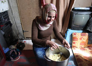 Food parcels contain staple items such as cooking oil, sugar, lentils, rice and pasta. Parcels are tailored for different family sizes and provide each person with 700 kcal per day for a month. Here, Darin Abdallah al-Mohammad cooks pasta for her family of four, who were displaced from Sbeineh. © 2015 UNRWA Photo by Taghrid Mohammad