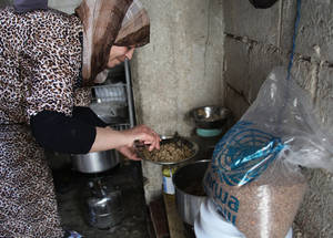 UNRWA food assistance is a critical source of nutrition for the 280,000 Palestine refugees who have been internally displaced in Syria. After fleeing Sbeineh in February 2013, Nadia Hussein – a mother of five – and her family were displaced four times before taking refuge in Sahnaya, Damascus. Here, Nadia cooks mujadara, using lentils and rice provided in the box. © 2015 UNRWA Photo by Taghrid Mohammad