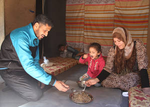 "Food assistance, made possible with the support of the UAE, helps Nadia and her family maintain important rituals in the midst of conflict and uncertainty. They eat mujadara in their room at the UNRWA Sahnaya collective shelter. ""It's the perfect meal with yoghurt,"" says Nadia. © 2015 UNRWA Photo by Taghrid Mohammad"