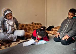 "UNRWA first met Aya and her family in late 2013. ""I was going back home from school with Maram, and I was wearing my brown shoes,"" said Aya. ""As we were walking the mortar exploded. The shoe just flew and my leg flew with it. I lost my leg – my leg was gone."" Here, Aya is pictured colouring in the living room, while her sister Maram (left) and her late brother Muhammad (right) look on. © 2013 UNRWA Photo by Carole Alfarah"