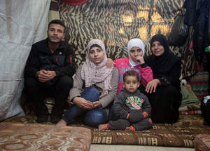 Mattresses are used as basic furnishings while people are temporarily displaced. This family of six living in an UNRWA collective centre in Jaramana camp found shelter in a converted school. With tarps, the classrooms have been subdivided into small living areas adjusted to the size of the family. Among the few belongings they have in their unit, mattresses insulate them from the cold. Jaramana camp. © 2015 UNRWA Photo by Taghrid Mohammad