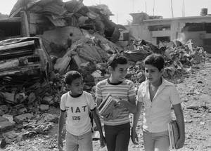 Children walk to school amid the rubble in Shatila camp, Lebanon. © 1982 UNRWA Archive Photo by George Nehmeh