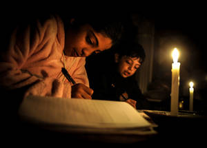 Children doing homework by candlelight as a result of electricity cuts in Gaza. © 2012 UNRWA Photo by Shareef Sarhan