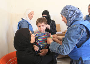 As part of its humanitarian activities in Yalda, UNRWA medical staff run a primary health point for Palestine refugees with the help of a medical officer, a nurse and a pharmacist. This medical worker is measuring a child's mid-upper arm circumference to check for signs of malnutrition. UNRWA Distribution Point, Yalda, Syria. © 2016 UNRWA Photo by Taghrid Mohammad
