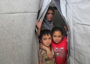 """نسرين عبدالله المصري لاجئة من فلسطين تعيش في أحد الملاجئ الجماعية التابعة للأونروا. وهي تقول """"بعد أن أصيب منزلي بقذيفة، انتقلنا إلى الملجأ الجماعي في جرمانا. وفي حين أن هذا ليس هو الخيار الأفضل، إلا أنه أفضل من العيش في الشارع"""". وتتمنى نسرين أن تتمكن من العودة إلى منزلها من أجل توفير مستقبل أفضل لطفليها. الملجأ الجماعي في جرمانا، دمشق، سورية، نيسان 2016. الحقوق محفوظة للأونروا، 2016. تصوير تغريد محمد."""