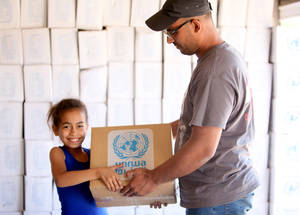 Although food is still available in most markets, inflation and restricted access mean that many families go hungry. To help them, in the last six months, UNRWA has distributed 235,616 food parcels containing rice, sugar, pasta, pulses, oil, powder milk and a sweet treat of halawa to Palestine refugees. These boxes cover a third of a family's recommended caloric intake for a month. Sahnaya Distribution Centre, Sahnaya, Rif Damascus, Syria, May 2016. © 2016 UNRWA Photo by Taghrid Mohammad
