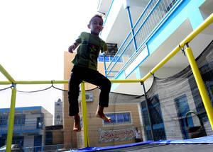 """يعيش عمر أبو دلاج (12 سنة) في بيت لاهيا شمال غزة. وكان عمر قد أصيب بجراح بالغة خلال الأعمال العدائية التي جرت عام 2008 وكان يتوجب عليه أن يبتر ذراعه. وخلال أسابيع المرح الصيفية، تقوم الأونروا وبشكل فاعل بتشجيع مشاركة الأطفال ذوي الإعاقات في أنشطتها وخدماتها من أجل تعزيز الإدماج الاجتماعي وتوفير فرص متساوية لهم للتعلم واللعب. ، يقول عمر مضيفا """"إن أكثر ما أحبه هي الترامبولين؛ فهي تجعلني أشعر كأنني طير يحلق في السماء"""".2016. تصوير هبة كريزم."""