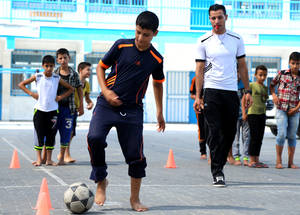 "Through the SFWs, UNRWA provides refugee children with a safe space to practice sports, as there are very few public sports facilities in Gaza. ""I have no place to play football except in the street – it is very dangerous,"" commented 14-year-old Hamza Essa, a ninth-grade student who lives in Beit Lahiya. ""During the SFWs, me and my friends have a place to play and charge energy, which also helps for a fresh start in the new upcoming school year."" © 2016 UNRWA Photo by Hiba Kreizim"