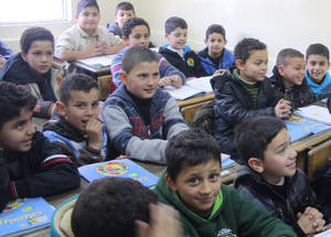 """The picture shows children attending a normal class at Nazzal Boys School. This is how they spend the whole school year sitting close to each other with very little room on the desk for them to use their textbooks"" said Roger Davies the Director of UNRWA Operations in Jordan. ""The situation in the Agency's 59 schools accommodated in rented buildings in Jordan is almost the same, which compromises the ability to actively engage in their education and raises concerns with regard to students and teachers' he"