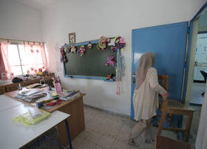 """I have to clean 15 classrooms and the entire school. When I clean a classroom I have to bring all the desks outside, clean the floor and put them inside again,"" said Kholoud Abdel Kader, the school attendant at Qusor School. ""Also, there is no drainage. I have to start from the top floor to the down floor to drain the water in the street."" © 2016 UNRWA Photo by Ahmad al-Ameen"