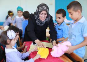 """""""كان لبرنامج [الإصلاح التربوي] أثرا إيجابيا على تغيير فن التعليم لدي كمعلمة – لقد بدأنا باستخدام العمل الجماعي والدراما ولعب الأدوار في التعليم، الأمر الذي كان له أثر إيجابي على السلوك وعلى مستوى التحصيل لدى الأطفال""""، تقول رجاء مرجان معلمة المرحلة الابتدائية الأساسية في غزة والتي دأبت على ممارسة التعليم لمدة 20 عاما. الحقوق محفوظة للأونروا، 2016. تصوير رشدي السراج."""