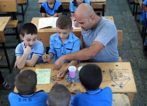 """""""قمنا بتغيير النهج بسبب برنامج التعليم الجامع""""، يقول محمد خضر أبو شمالة معلم المرحلة الابتدائية الأساسية في غزة مضيفا """"واليوم، فإنني أستخدم مجموعة من الأساليب التربوية، ويقوم كافة الطلبة عندي بالمشاركة بنشاط في قلب العملية التعلمية. إنني أعمل على تطوير كافة جوانب تحصيل الطلبة، بما في ذلك نموهم الجسدي والاجتماعي والنفسي، ويعود الفضل في ذلك للألعاب المتنوعة والأنشطة الترفيهية"""". الحقوق محفوظة للأونروا، 2016. تصوير رشدي السراج."""