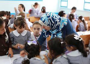 """""""عملت برامج تدريب الإصلاح التربوي على تعزيز ممارساتي التعليمية وذلك من خلال إعادة ترتيب الطلبة في الصف والعمل الجماعي وزيادة مشاركة الطلبة في عملية التعلم""""، تقول فاطمة أكرم حرزالله معلمة المرحلة الابتدائية في غزة. وتضيف فاطمة: """"أصبح الأطفال الآن يسألون ويناقشون ويحتفظون بآرائهم الخاصة. إنني أشعر بالسعادة حيث أن أطفالنا معدون إعدادا أفضل من أجل المستقبل"""". الحقوق محفوظة للأونروا، 2016. تصوير رشدي السراج."""