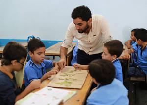"""يقول مشرق جبريل أبو سيدو معلم المرحلة الأساسية في غزة: """"من خلال برامج الأونروا، قمت بتحسين مقدرتي على إيصال المواد التعليمية الصعبة من خلال نهج تواصلي مترابط لكافة الموضوعات. إنني أشعر بمسؤولية أكبر تجاه طلبتي مثلما أحس بالفخر لرؤيتهم مستعدين للمستقبل وجاهزين لتجاوز تحديات الحياة"""". الحقوق محفوظة للأونروا، 2016. تصوير رشدي السراج."""