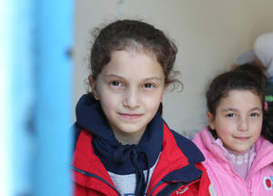 """My school feels like my home and I am happy in Jordan"", says Amira* in flawless English. The school has instituted a 'buddy system' where children from Syria are paired with older students from Jordan to integrate them and prevent them from being bullied.  Pictured here with her younger sister, Amira arrived in Jordan a year ago. She was the star of Human Rights Day and has consistently ranked first in her class."