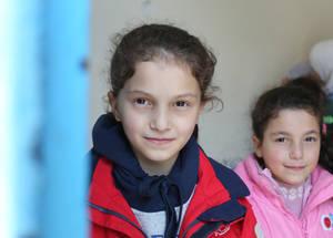 """""""مدرستي تبدو مثل بيتي وأنا سعيدة بوجودي في الأردن""""، تقول أميرة بلغة إنجليزية تخلو من الأخطاء. لقد قامت المدرسة بإرساء """"نظام الصديق"""" يعمل على جمع الأطفال من سورية بطالبات أكبر سنا من الأردن بهدف إدماجهن ومنعهن من التعرض للتنمر. وتظهر في الصورة أميرة، التي وصلت إلى الأردن قبل سنة، مع شقيقتها الصغرى. وقد كانت أميرة نجمة يوم حقوق الإنسان وكانت دائما الأولى على طالبات صفها"""