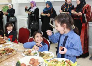 أغذية تقليدية من سورية. يتم تشجيع الأمهات القادمات من سورية بقضاء بعض الوقت في المدرسة لمعرفة البيئة الجديدة التي يعيش فيها أطفالهن وللقاء الأمهات الأردنيات. وفي هذا الفضاء المجتمعي الآمن، فإن أمهات الطالبات في غالب الأحيان يقمن بطهي أطباق تقليدية سورية