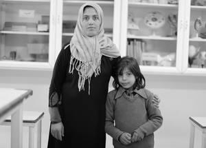 معلمة مع طالبتها الفلسطينية من سورية. في مدرسة الأمير حسن الأولى للبنات، تلقت المعلمات تدريبا متخصصا من منظمات المجتمع المحلي يهدف إلى تسليحهن بمهارات تحديد الطالبات اللواتي قد يعانين أكاديميا أو عاطفيا وسبل مساعدتهم. وهنالك حاجة للمزيد من مثل هذه الدورات التدريبية. مدرسة الأمير حسن الأولى للبنات، جنوب عمان