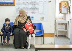 A mother and her two children at an UNRWA health centre in Gaza City. As a result of the Family Health Team implementation, health centres have seen less congestion and crowding in waiting areas, which has been met with a positive response from community members and families. © 2016 UNRWA Photo by Hussein Jaber