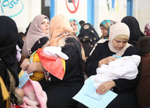 مرضى لاجئي فلسطين في غرفة الانتظار بمركز صحي ماركا في عمان، الأردن. لقد نتج عن نهج فريق صحة الأسرة تحسن ملموس في جودة عملية تقديم خدمات الرعاية الصحية للاجئي فلسطين، بما في ذلك ارتفاع في معدل النساء الحوامل اللواتي كن قادرات على إجراء أربع زيارات لرعاية ما قبل الولادة على الأقل، علاوة على زيارات ما بعد الولادة من قبل الأمهات ومواليدهن الجدد. الحقوق محفوظة للأونروا، 2016. تصوير أحمد خضر